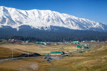 Hotels and resorts at foothills of Snow Covered Himalayan Mountains and pine tree lands in Gulmarg, Jammu and Kashmir, India Stok Fotoğraf