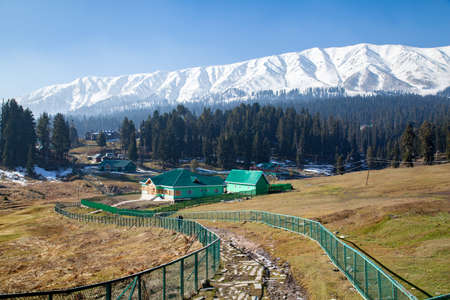 Snow Covered Himalayan Mountains and fencing covered waterways in Gulmarg, Jammu and Kashmir, India