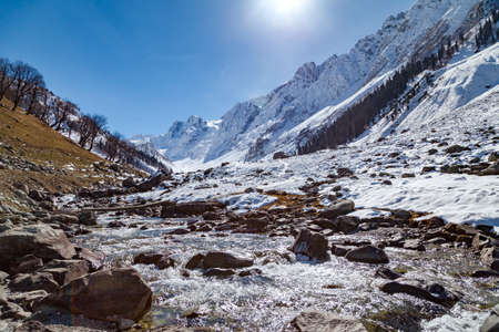 Warm sunrays creates a water stream by melting the snow of Himalayan Mountains near Sonmarg, Jammu and Kashmir, India