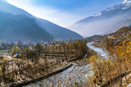 A water stream flowing down the terrains of Himalayan Mountains and passing through a village near Sonmarg, Jammu and Kashmir, India