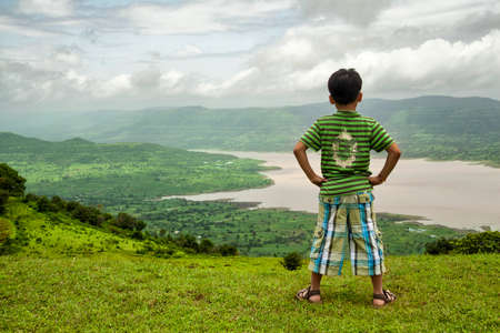 Mahabaleshwar, Maharashtra, India - August 17, 2012 : Back view of little boy looking at a scenic view of Mountains and river. Editorial