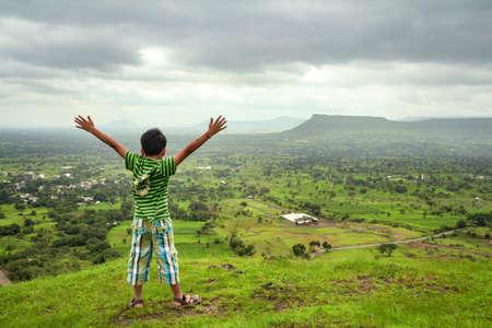 Mahabaleshwar, Maharashtra, India - August 17, 2012 : Cheerful little boy having fun against beautiful green mountains at way to Mahabaleshwar.
