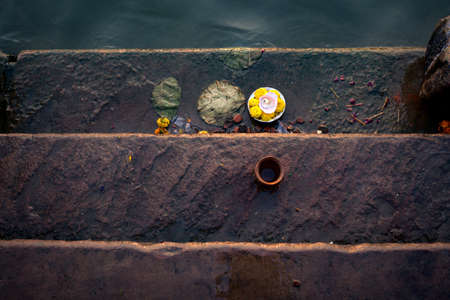 lamp and flowers on the stairs for worship in morning time, varanasi, uttar pradesh, india.