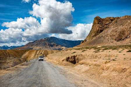 View of arid landscape of highway road for travel with big mountain and blue sky as background, Leh Ladakh - India
