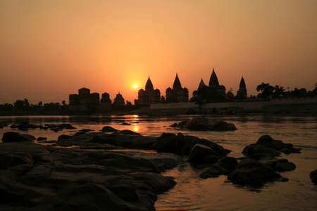 Cenotaphs (Chhatris) on the bank of the Betwa River at sunset. Orchha, Madhya Pradesh, India