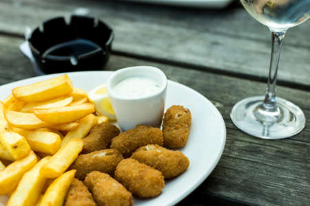 a plate of scampi and chips on a wooden table