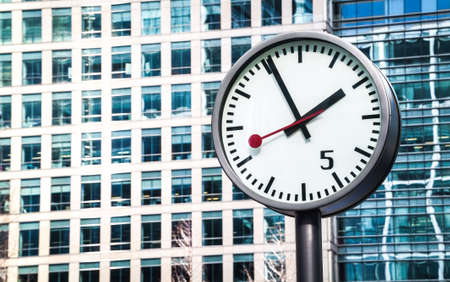 LONDON, UK - MARCH 16, 2014: Closeup of one of the famous Canary Wharf clocks outside One Canada Square. 스톡 콘텐츠