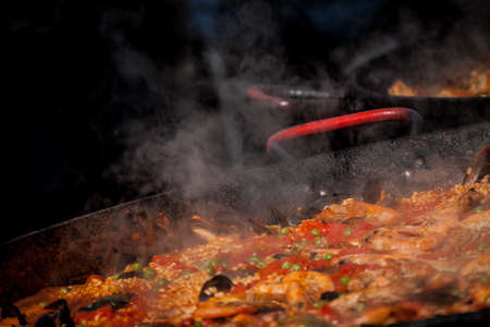a steaming hot dish being cooked in a market Stock Photo