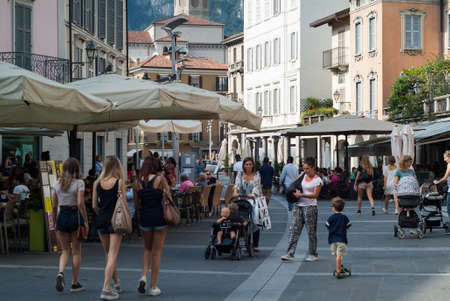 Lecco, Italy - September 1st, 2015: pedestrians walking past shops and restaurants in a central street in Lecco, Italy, photographed on September 1st, 2015.