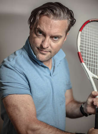 portrait of a handsome man with a tennis racket