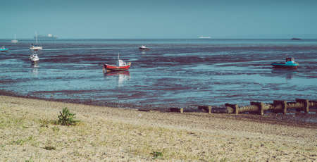 small boats photographed during low tide in Shoeburyness, Essex, UK