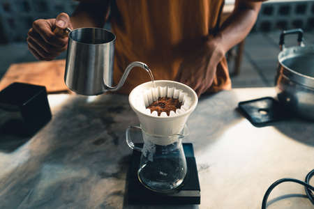 Drip coffee, barista pouring water on coffee ground with filter at home