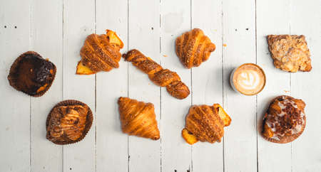 Freshly baked traditional bread on wooden table ,baked croissants in a bakery