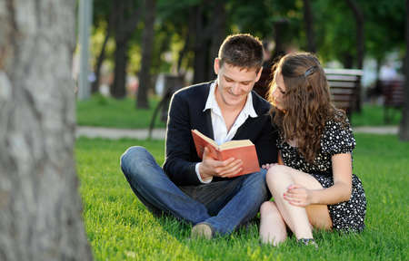 Boy and girl reading a book sitting on the grass in the park photo