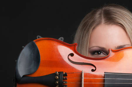 girl holding a violin and looking through it photo