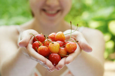 she holds a handful of cherries outside Stock Photo - 16143105