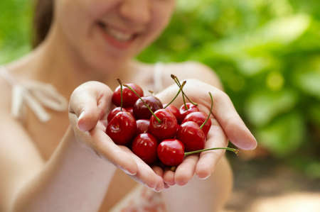 she holds a handful of  red cherries outside Stock Photo - 16143021