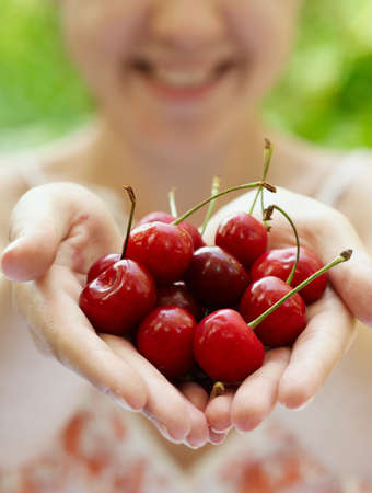 Smiling girl holding a handful of red cherries 写真素材