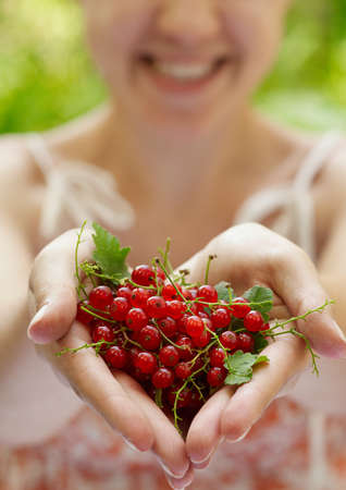 Smiling girl holding a handful of red currants Stock Photo - 16142957