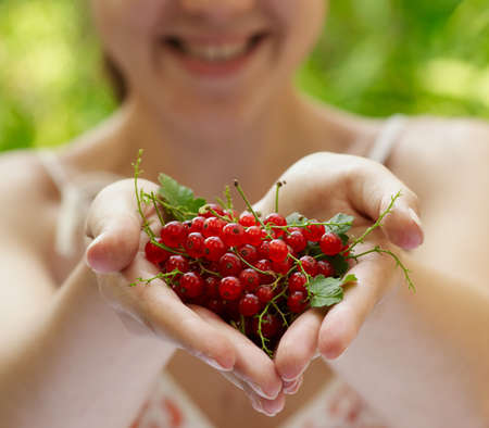 Girl holding a handful of red currants Stock Photo - 16142885