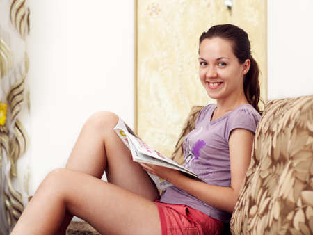 The girl is sitting on the sofa and reading a newspaper Stock Photo - 16143014