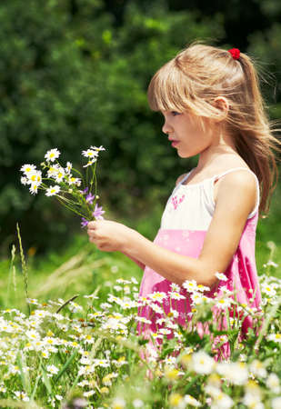 The little girl is stanging in the grass and holding a bouquet photo