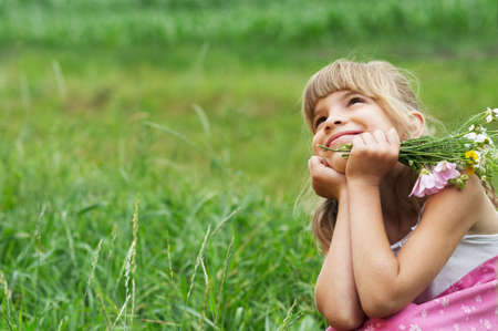 The little girl is sitting in the meadow and dreaming photo