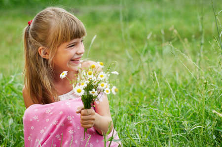 The happy little girl in the green grass photo
