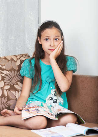 little girl sitting: The upset girl is sitting on the sofa with the magazine
