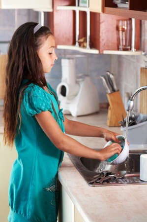 dirty dishes: caucasian girl washing dishes in the kitchen