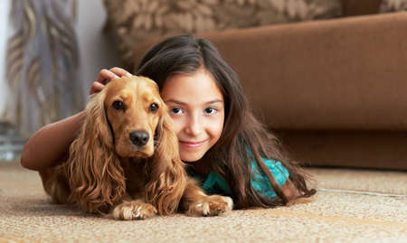 carpet: The girl is lying in the floor with the dog