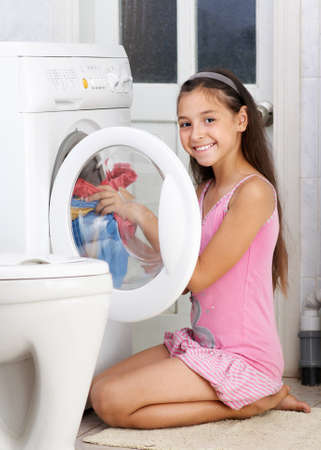 The young girl is washing clothes in the bathroom