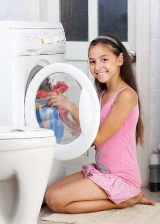 lavando ropa: La joven está lavando ropa en el baño