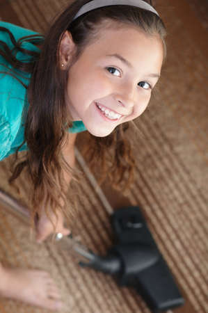 The smiling girl is vacuuming  the carpet photo