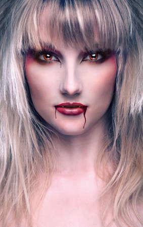 portrait of a beautiful blond girl vampire with bloody streaks