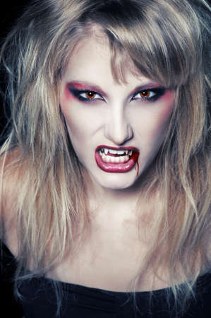 The portrait of a blond girl vampire with bloody streaks photo