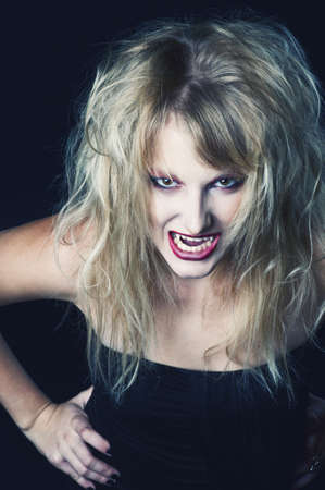 blond streaks: The portrait of a blond girl vampire with bloody streaks Stock Photo