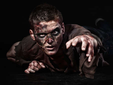 deadman: The scary zombie is lying in the studio and stretching Stock Photo