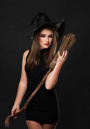 escoba: La bruja con una escoba en un vestido negro en el estudio de