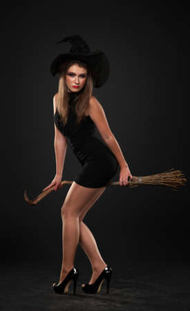 curtsy: The girl with the broom is standing in the studio Stock Photo