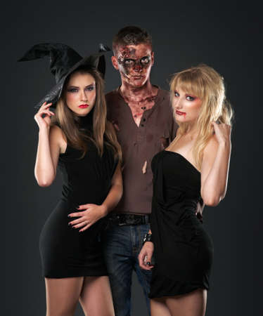 zombie vampire and witch are standing whith pumpkin in the dark studio photo