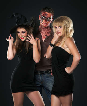 zombie vampire and witch are happy and standing in the studio photo