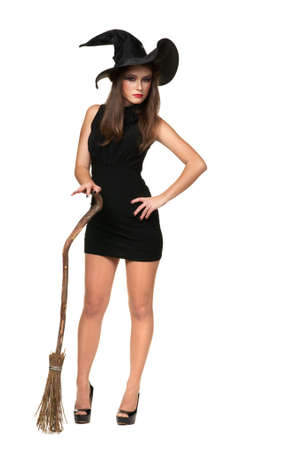 The  beautiful witch with a broom in a black dress photo