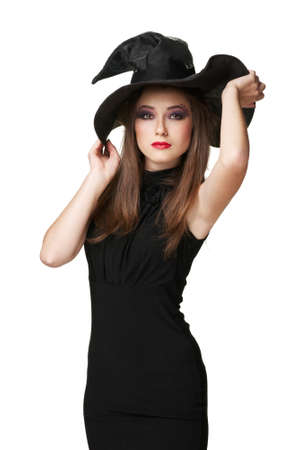The  young brunette witch is standing in a black dress photo