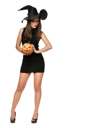 The beautiful witch holds an orange  pumpkin