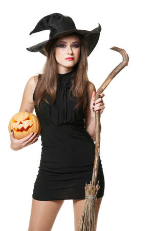 The  young serious brunette witch with a broom and pumpkin photo