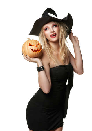 The beautiful witch holds an orange pumpkin in a black hat