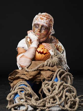 flatly: The sad mummy iin the studio and holding the  pumpkin Stock Photo
