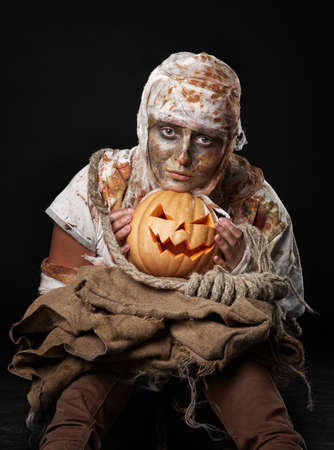 flatly: The boring  mummy iin the studio and holding the  pumpkin