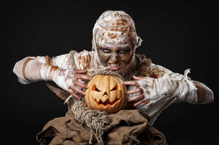 scary mummy holding the pumpkin in the studio photo